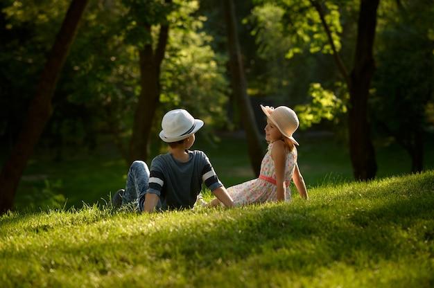 サマーパークでの子供のロマンチックなデート、友情、初恋。草の上に座っている気球を持つ少年と少女。屋外で楽しんでいる子供たち、幸せな子供時代