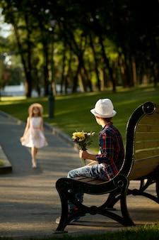 サマーパークでの子供のロマンチックなデート、友情、初恋。ベンチで女の子を待っている花を持つ少年。屋外で楽しんでいる子供たち、幸せな子供時代