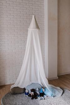 Детская комната оформлена в серых, голубых и белых тонах с балдахином и подушками на полу.