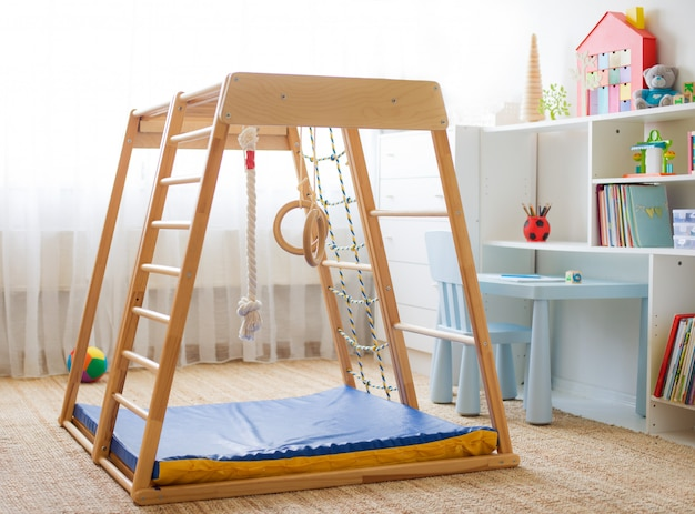 Children's room with a wooden sports complex with stairs, rings and a rope.