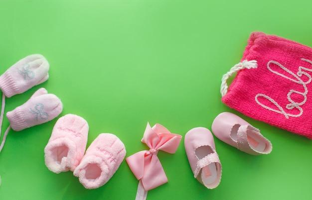 어린이 신발은 밝은 녹색 배경 상위 뷰에 놓여 있습니다. 텍스트를위한 공간입니다. 아기 슬리퍼.
