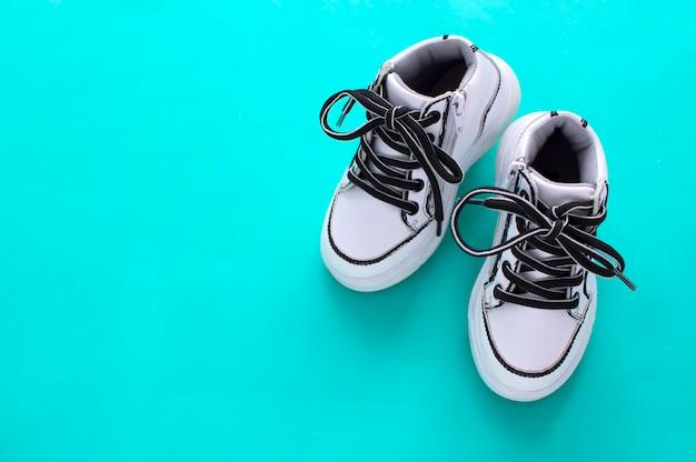 어린이 신발. 운동화, 파란색 배경에 끈이 달린 운동화. 스포티한 라이프 스타일의 개념입니다. 복사를 위한 평면 공간입니다. 위치. 평면도입니다.