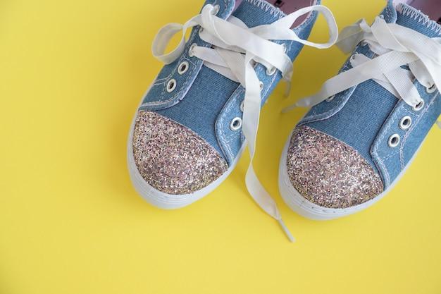 黄色の背景にひも付きの子供の靴