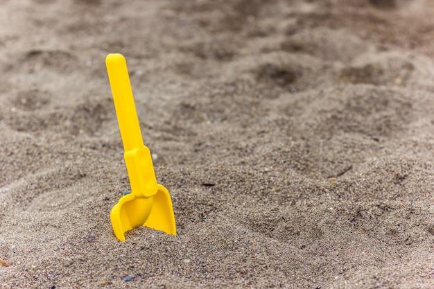 ビーチの砂の中の子供のシャベル