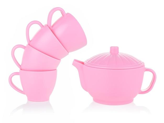 어린 이용 작은 머그컵과 분홍색 주전자가 흰색 배경에 서로 위에 서 있습니다.