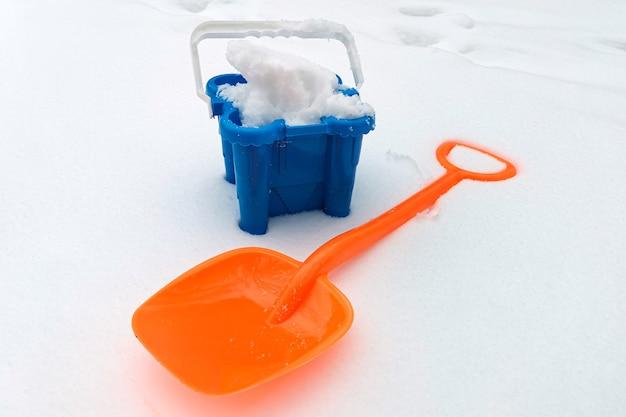 Детская лопата для снега и ведро, наполненное снегом на заснеженной территории. зимний активный отдых, аксессуары для детских развивающих игр со снегом. зимние развлечения