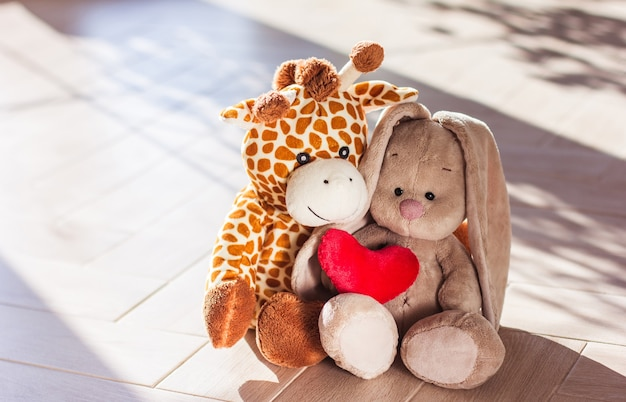 Children's soft plush toy giraffe and bunny sit on wooden background, hard light and shadow
