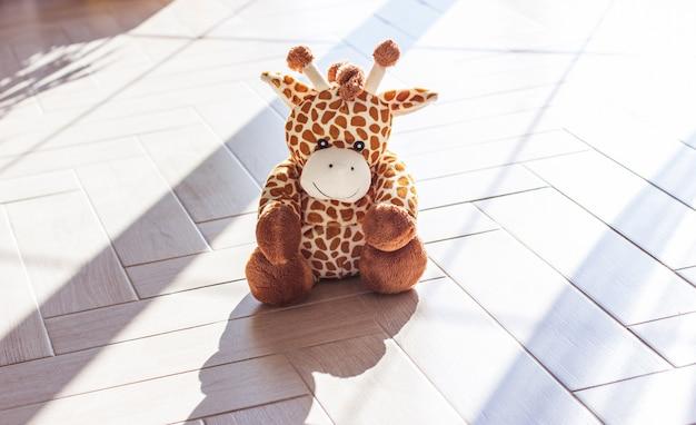 어린이 부드러운 봉제 장난감 기린 나무 배경, 하드 빛과 그림자에 앉아