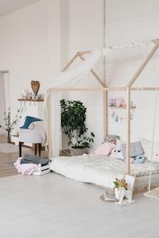 집 형태의 세련된 어린이 침대. 회색 베개가 있는 스칸디나비아 스타일 침실. 스칸디나비아 스타일의 아늑한 어린이 침실