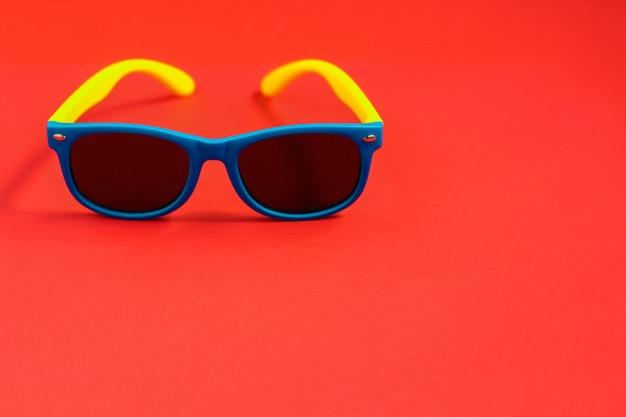 赤の背景に子供用サングラス。夏の休日のコンセプト、ミニマリズム