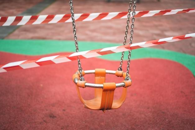 雨の日にコロナウイルスを閉鎖するためのテープに囲まれた公園での子供たちのブランコ。