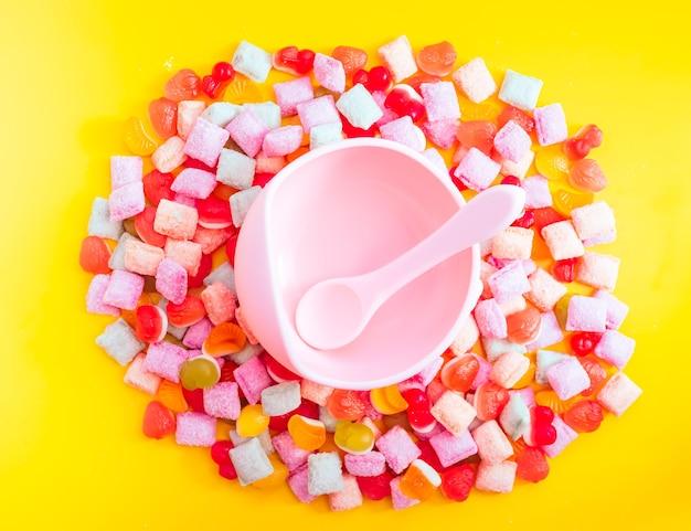 スプーン付き子供用食器シリコンボウル。離乳食、子供用食器を提供しています。ピンクのシリコンボウルとスプーンは、お菓子とマーマレードの山の中にあります。明るくカラフルな写真をフラットに