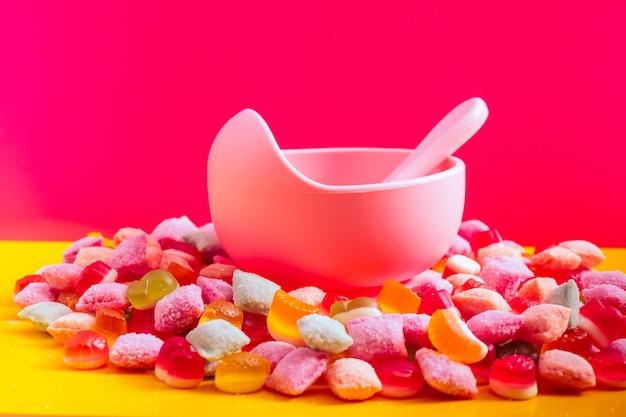 スプーン付き子供用食器シリコンボウル。離乳食、子供用食器を提供しています。ピンクのシリコンボウルとスプーンは、お菓子とマーマレードの山の中にあります。明るくカラフルな写真。