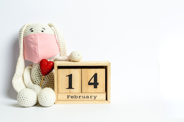 Детская игрушка в защитной медицинской маске с красным блестящим сердечком возле календаря с датой 14 февраля