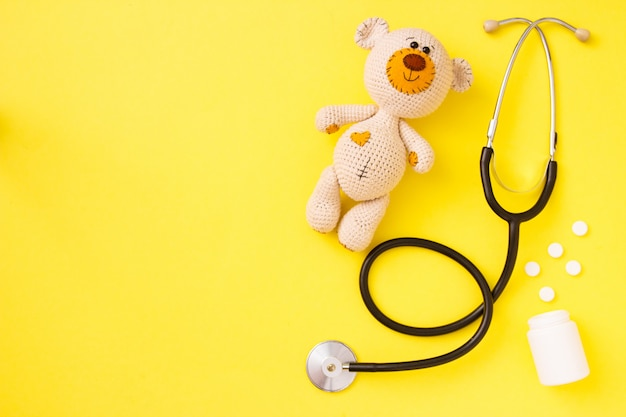 Children's toy teddy bear amigurumi with stethoscope on yellow