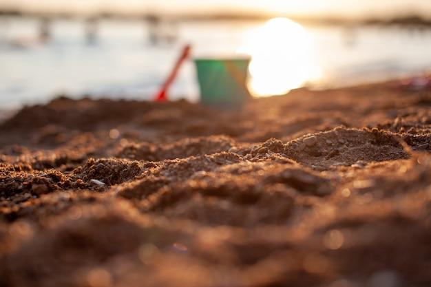 砂で遊ぶための子供のおもちゃ。日没時のビーチでプラスチック製のバケツと熊手。夏、家族の休日や休暇の概念。バケツは焦点が合っていません。砂に焦点を合わせる
