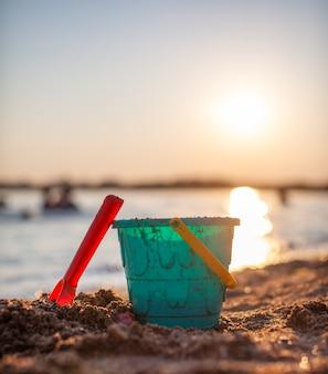 砂で遊ぶための子供のおもちゃ。日没時のビーチでプラスチック製のバケツと熊手。夏、家族の休日や休暇の概念。