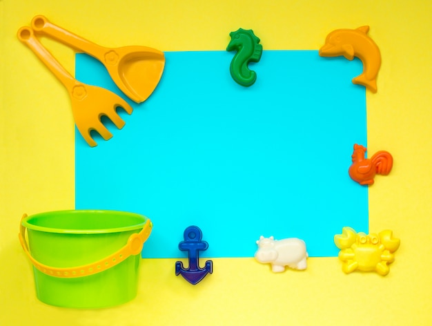 Children's toys for sand on yellow, space for copy space.