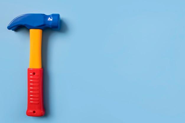 Детская обучающая игрушка пластиковый молоток на однородном синем фоне copyspace