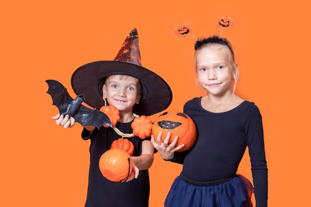 Children's trick or treat in a halloween costume. little boy in a wizard's hat holding an orange pumpkin-shaped basket and a black bat and a girl holding a painted pumpkin on an orange background.