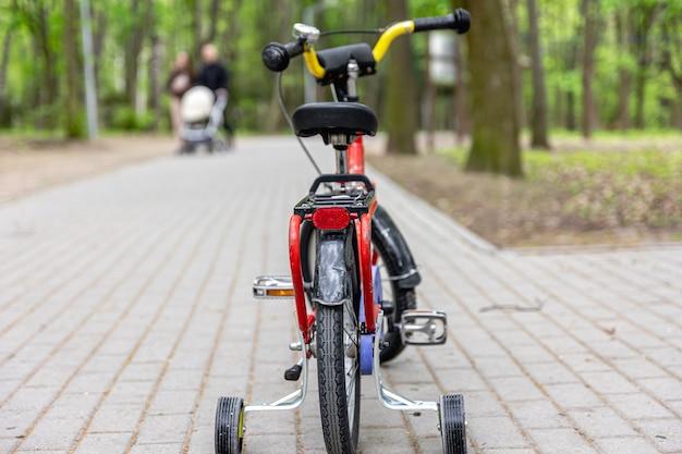 Triciclo per bambini nel parco su uno sfondo sfocato