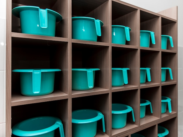 Children's turquoise pots stand in a row on a rack in the kindergarten