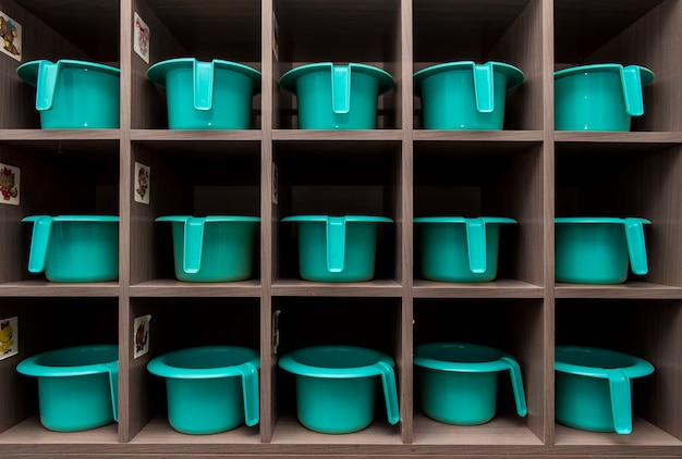 Children's turquoise pots stand in a row on a rack in the toilet kindergarten
