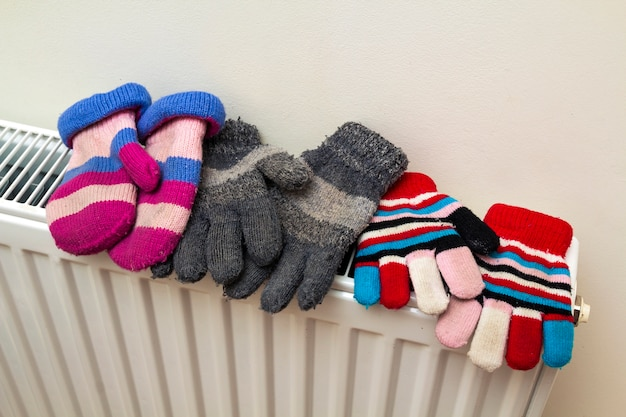 Children's warm hand knitted striped woolen gloves drying on hea
