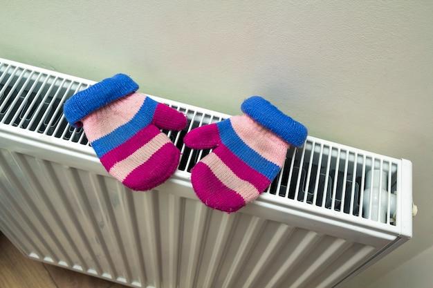 Children's warm hand knitted striped woolen gloves drying on hea