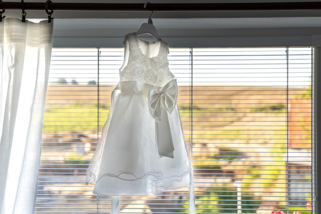 Children's wedding dress hanging on window cornices.