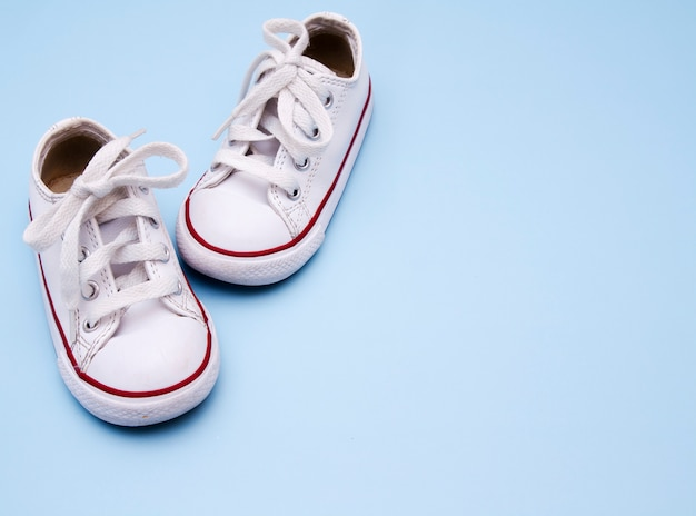 Children`s white sneakers on a blue background. copy space for text about baby shoes, clothes, walks.