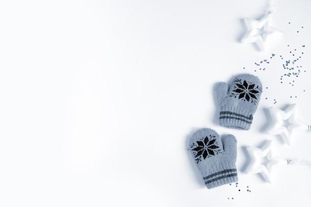 子供の冬の手袋と白い背景の上の白い星。