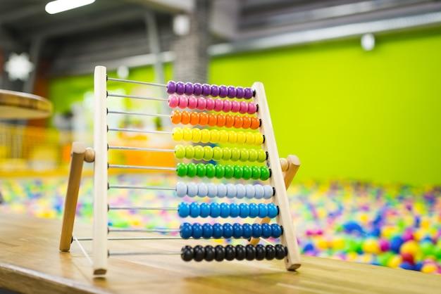Детская деревянная игрушка счеты яркого цвета на поверхности игровой комнаты