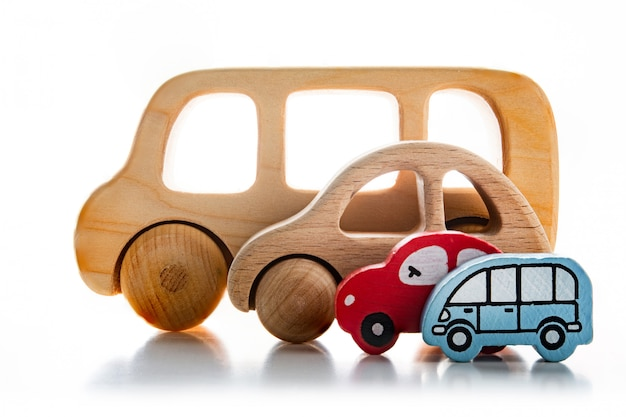 Children's wooden cars on a white wall.