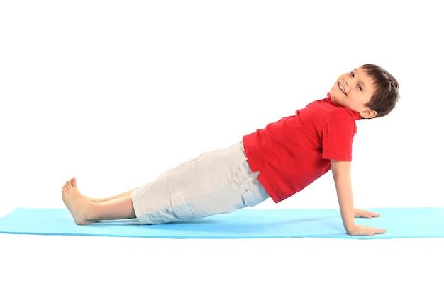 어린이 요가. 어린 소년은 운동을합니다.