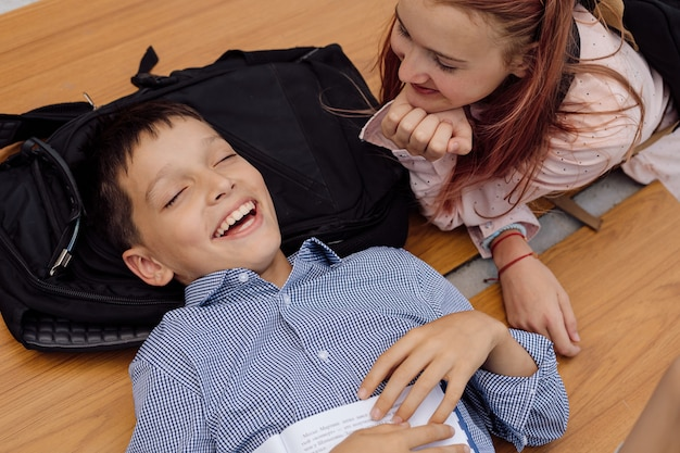 Children and schoolchildren have fun after school with backpacks on their backs