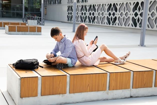어린이 학생은 학교 운동장에 등을 맞대고 앉아 모바일 장치를 사용하여 숙제를 합니다.