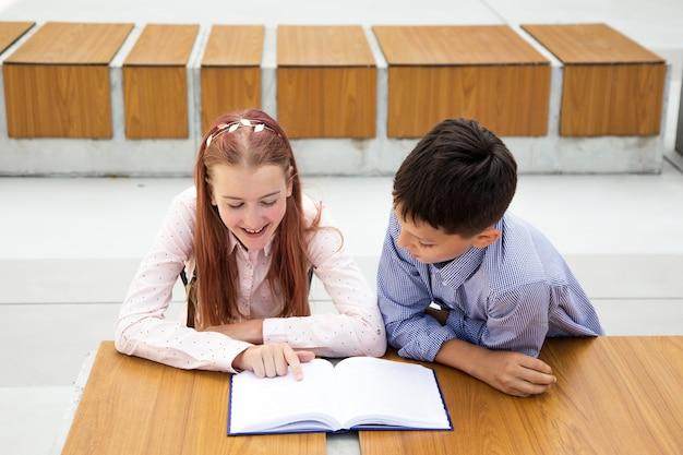 Дети, школьники, подростки читают в школьном дворе школы на деревянной скамье. мальчик и девочка увлечены книгой