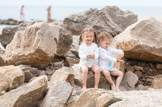 Children on the sea beach. twins sitting against stones and sea water.