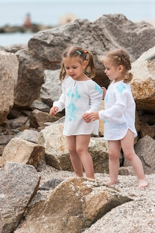 Children on the sea beach. twins standing against stones and sea water.