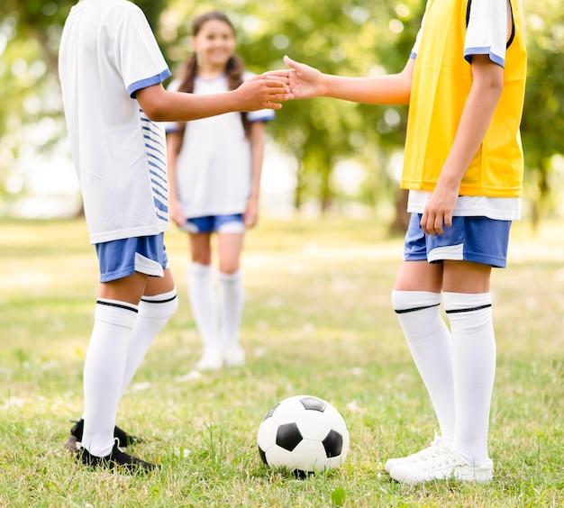 I bambini si stringono la mano prima di una partita di calcio all'aperto