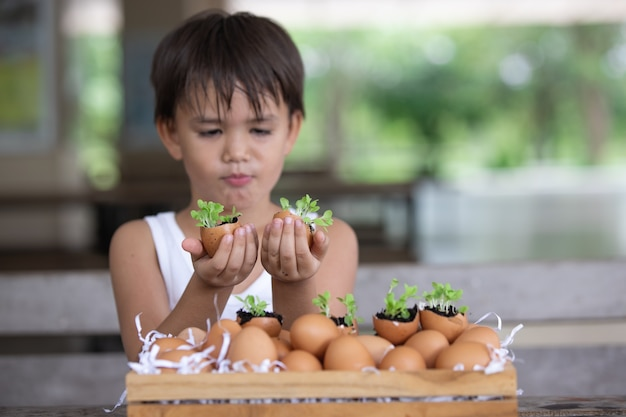 卵殻にやさしいコンセプトから育つ苗を見せてくれる子供たち社会問題