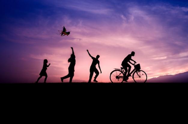 Дети силуэты играют с воздушных змеев и велосипедистов на закате.