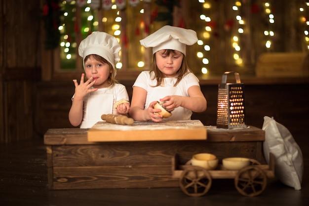 어린이 자매는 어린 시절의 개념을 늘리기 위해 롤링 핀으로 요리합니다.