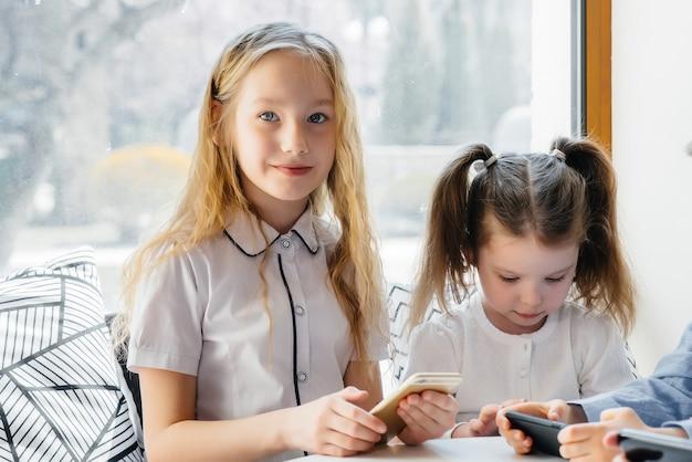 Дети сидят за столиком в кафе и вместе играют в мобильные телефоны. современные развлечения.