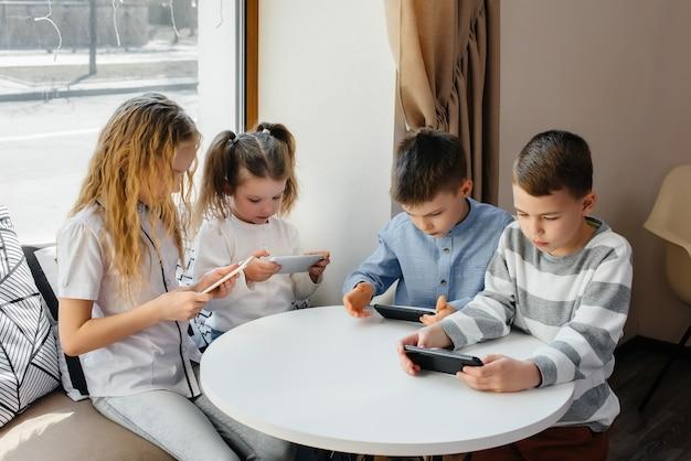 子供たちはカフェのテーブルに座って、一緒に携帯電話をします。モダンエンターテインメント。