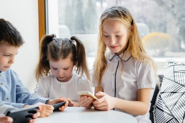 아이들은 카페 테이블에 앉아 함께 휴대폰을 즐깁니다. 현대적인 엔터테인먼트.