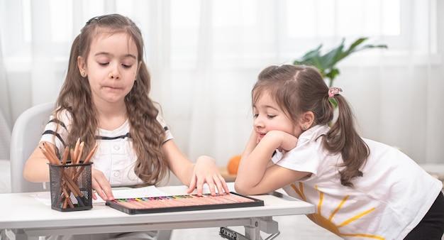 子供たちはテーブルに座って宿題をします。ホームスクーリングのコンセプト。