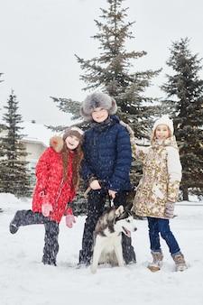 Дети сидят на снегу и гладят собаку хаски. зимой дети выходят на улицу и играют с хаски. гулять по парку зимой радость и веселье, собака хаски с голубыми глазами. россия, свердловск, 28 дек 2017 г.