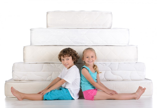 Children sit near the white mattresses.